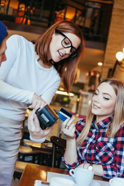 Young woman paying for restaurant with credit card.